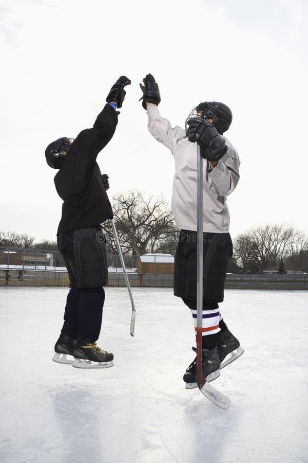 Fiving dei giocatori di hokey alto. fotografie stock libere da diritti