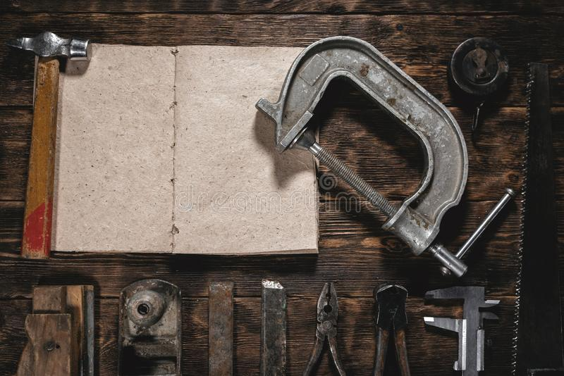 Fix list. To do list mock up. Construction handbook with blank pages and old construction tools on a wooden workbench flat lay background. Carpentry. Woodwork royalty free stock photo