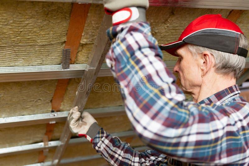 Fixação do metal da parede do emplastro do Drywall Homem que mantém a régua do metal contra o quadro do metal no teto inacabado d foto de stock royalty free