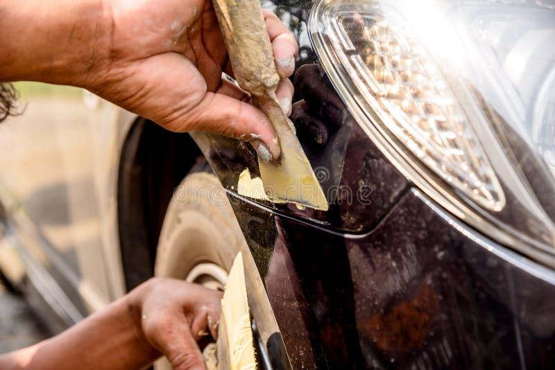 a fixação do reparador do trabalhador do mecânico riscou no corpo de carro e no prepa fotografia de stock royalty free