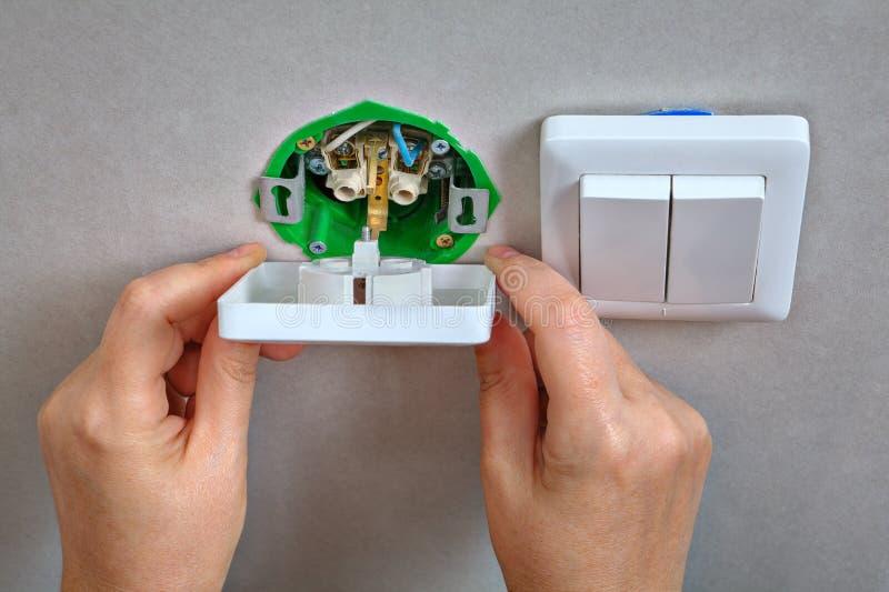 Fixa elektriskt vägguttag och den ljusa strömbrytaren, elektriker han fotografering för bildbyråer