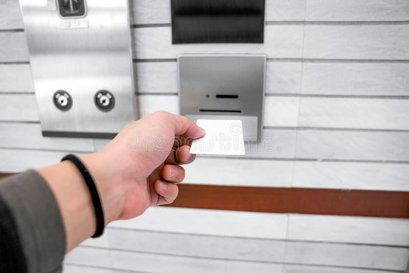 fixando o controle de acesso do elevador ou do elevador, a mão do homem está guardando uma configuração do cartão chave até a ins imagens de stock