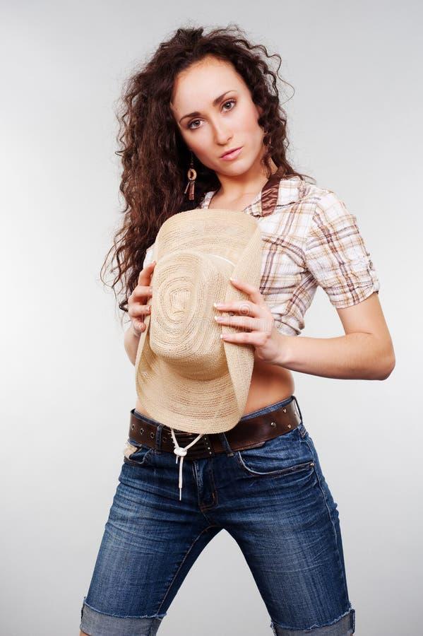 Fixation attrayante de cow-girl son chapeau photographie stock libre de droits