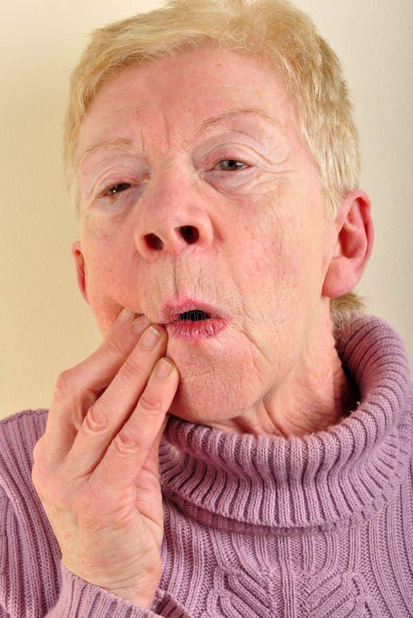 fixation de dame âgée son mâchoire douloureux photo libre de droits