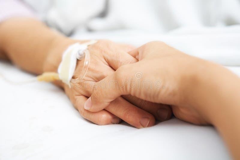 Fixation de descendant sa main de mère dans l'hôpital photographie stock