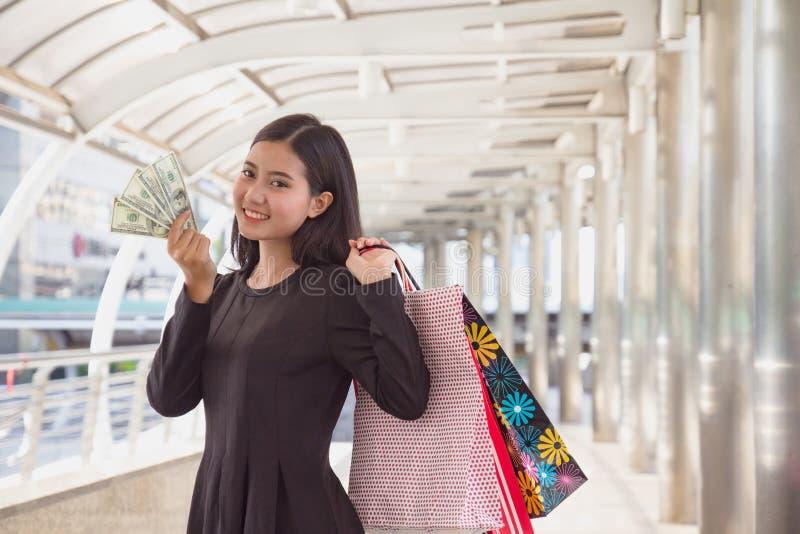 Fixation de jeune femme par la carte de cr?dit Fille asiatique heureuse avec des sacs ? provisions au mail souriant regardant la  photographie stock