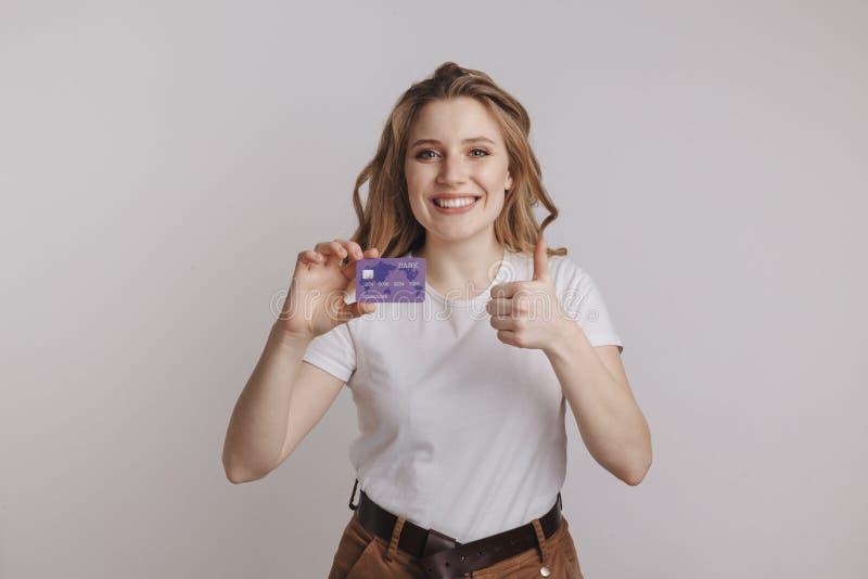 Fixation de sourire de femme par la carte de crédit Portrait d'isolement image libre de droits