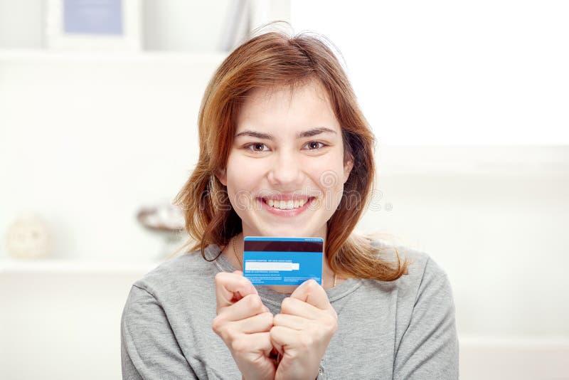Fixation heureuse de jeune femme par la carte de crédit image libre de droits
