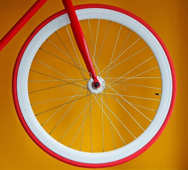 Fixed gear bicycle wheel with thin red tire and white wide rim royalty free stock photography