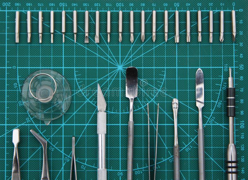 Electronics repair on the desktop with tools top view. Fixer electronics neatly arranged on the substrate of the green. Center lined with screwdriver, tweezers royalty free stock photo