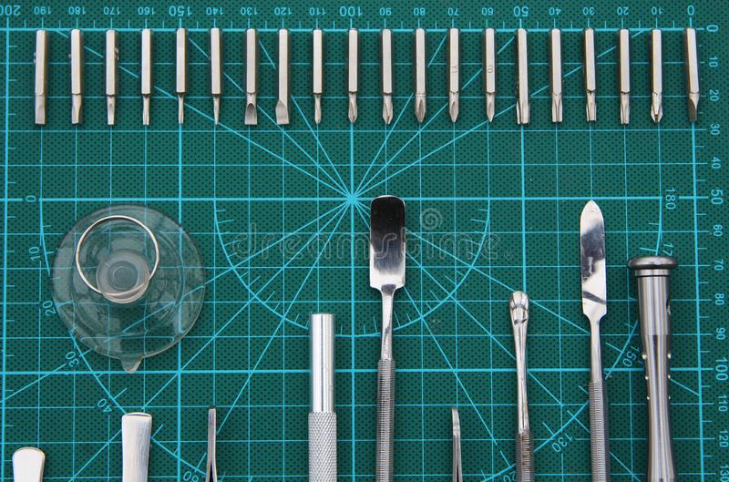 Electronics repair on the desktop with tools top view. Fixer electronics neatly arranged on the substrate of the green. Center lined with screwdriver, tweezers royalty free stock image