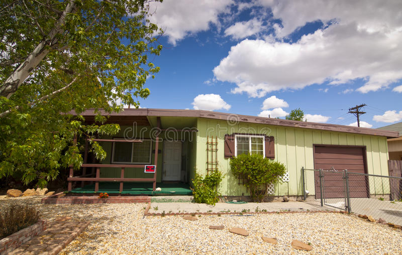 Fixer Upper House. Older Fixer Upper House with blue sky and clouds stock image