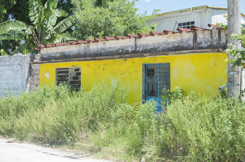 Fixer upper. LAS CHOAPAS, MEXICO - JULY 19, 2014: A small yellow concrete house sits in bad condition with broken windows and overgrown weeds in Las Choapas stock photography