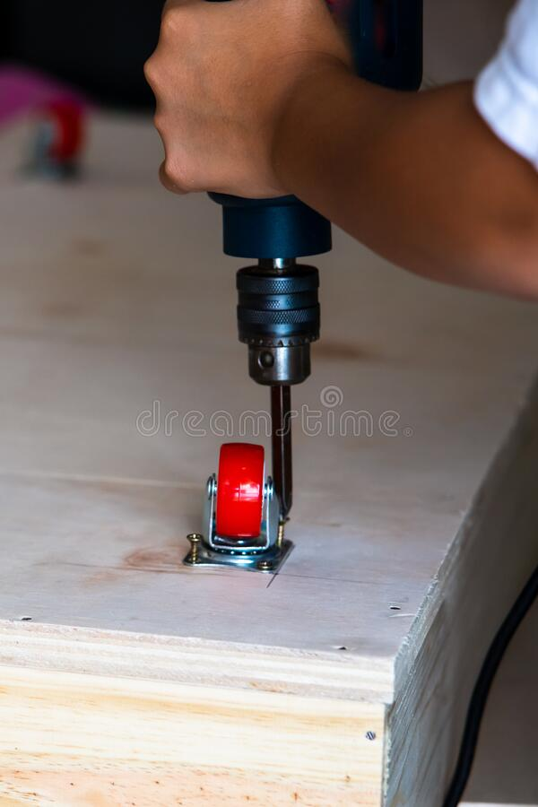 Fixing castor wheel to the wooden plywood, furniture making stock image