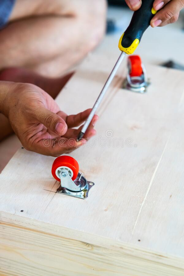 Fixing castor wheel to the wooden plywood, furniture making stock photography