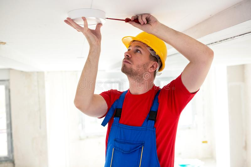 Fixing of ceiling light with screwdriver royalty free stock photo