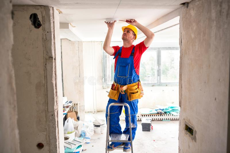 Fixing of ceiling light with screwdriver royalty free stock photos