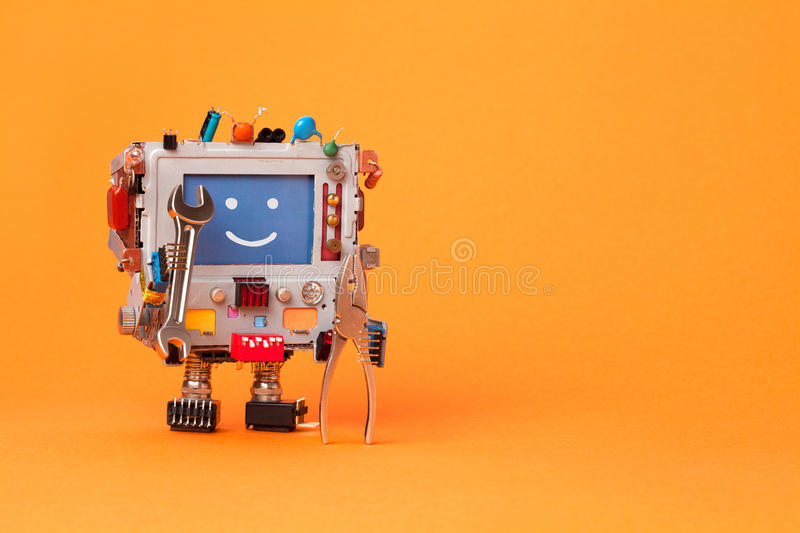 Fixing computer concept. Robotic electrician with hand wrenches for repair. Colorful display toy, smile message blue. Monitor. Service system communication royalty free stock photo