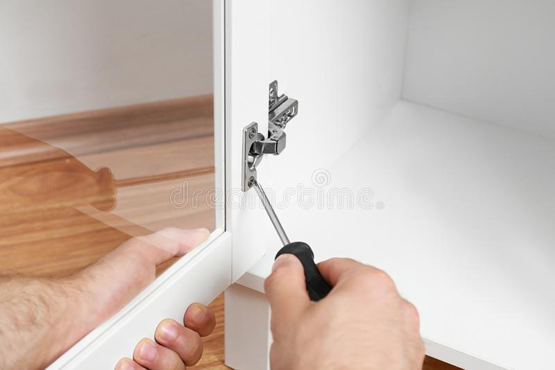 Fixing door angle hinge of wooden cabinet, closeup view. Man fixing door angle hinge of wooden cabinet, closeup view stock photo