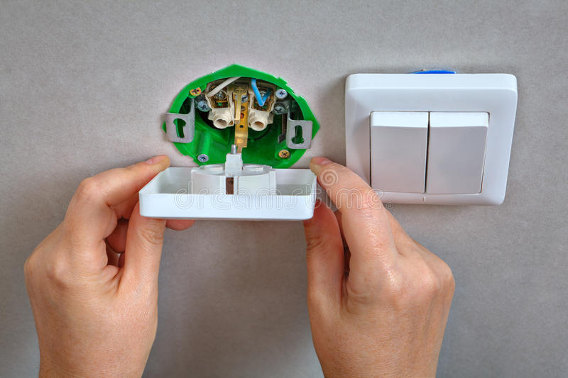 Fixing electrical wall outlet and light switch, electrician han stock image