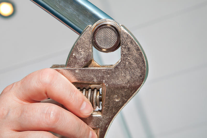 Fixing Faucet Aerator, using adjustable wrench plumber, hands h. Replace a Sink Aerator using an adjustable plumbing spanner , hands plumber close-up stock images