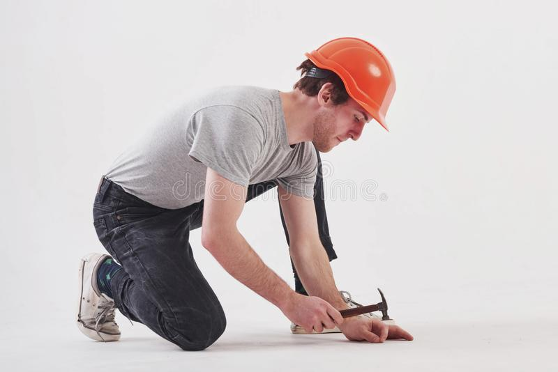 Fixing the floor. Man in casual clothes and orange colored hard hat have some work using hammer. White background royalty free stock photo