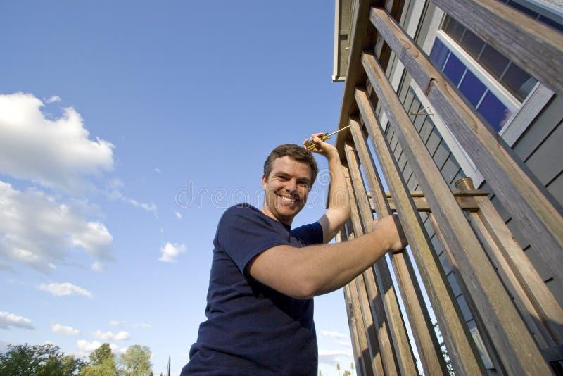 fixing happy horizontal house man στοκ φωτογραφία με δικαίωμα ελεύθερης χρήσης