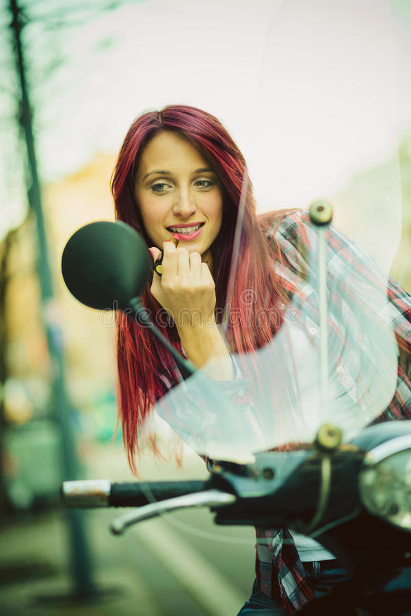 Fixing makeup on motorcycle. Young beautiful woman on motorcycle fixing her make up stock photo