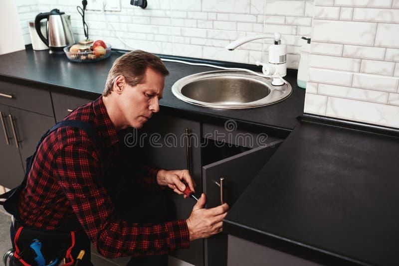 Fixing sink process. Seniour handyman repairing washbasin royalty free stock photography