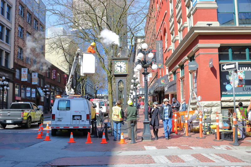 Fixing the Steam Clock and Gastown District in Vancouver, Canada. Wide on city work crew cleaning and fixing the famous steam clock in Vancouver`s Gastown royalty free stock photography