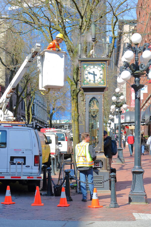 Fixing Vancouver`s Steam Clock. City work crew clean and fix the famous steam clock in Vancouver`s Gastown district in preparations for the busy tourist season stock photos