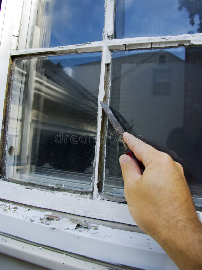 Fixing Window. Closeup on hand removing old window glazing with a chisel royalty free stock images