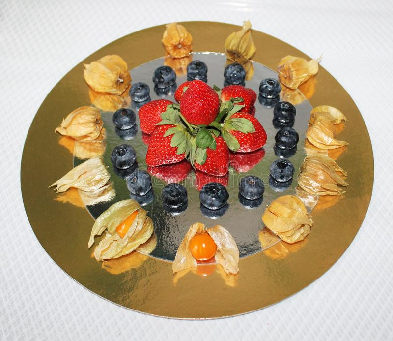 Photo composition of strawberries, blueberries and physalis stock photo
