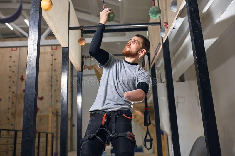 Fizycznie rzucający wyzwanie boulderer naprawiania specjalny wyposażenie w górę przy barem zdjęcie royalty free