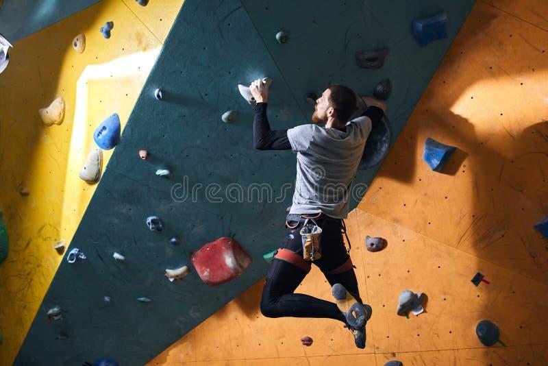 Fizycznie rzucający wyzwanie mężczyzna ćwiczy nowego krańcowego hobby w bouldering gym zdjęcie royalty free