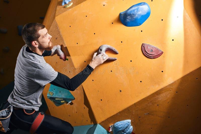 Fizycznie rzucający wyzwanie mężczyzny pięcie na sztucznej colourful skały ścianie obraz stock