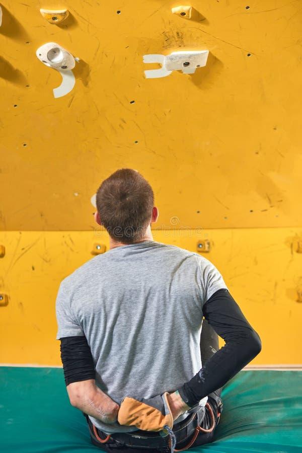 Fizycznie rzucający wyzwanie sportowa obsiadanie przy trzaska ochraniaczem i patrzeć skały ścianę obraz stock