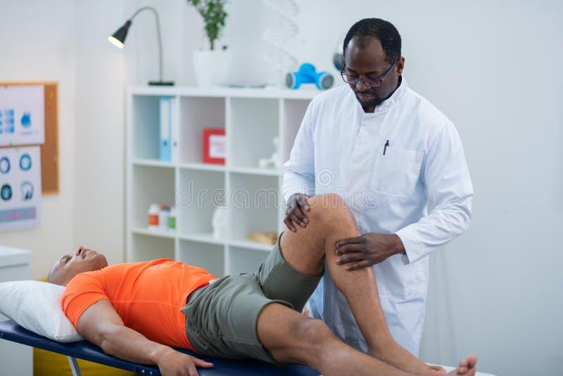Fizyczny terapeuta egzamininuje kolano kłama blisko on sportowiec obrazy royalty free