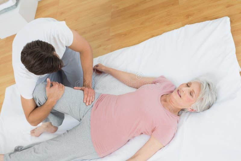 Fizyczny terapeuta egzamininuje starszą kobiety nogę obraz stock