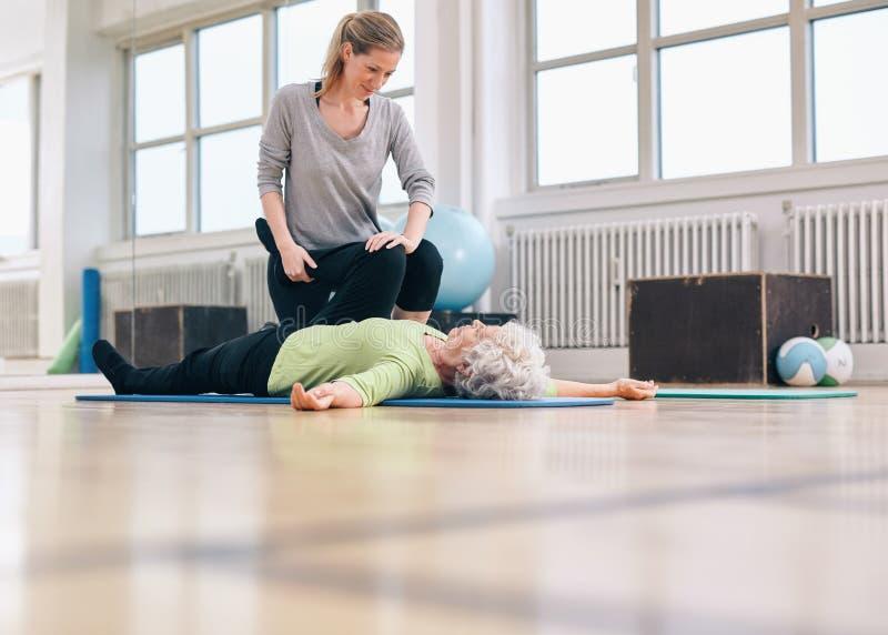 Fizyczny terapeuta pomaga starszej kobiety z nogi ćwiczeniem zdjęcie royalty free