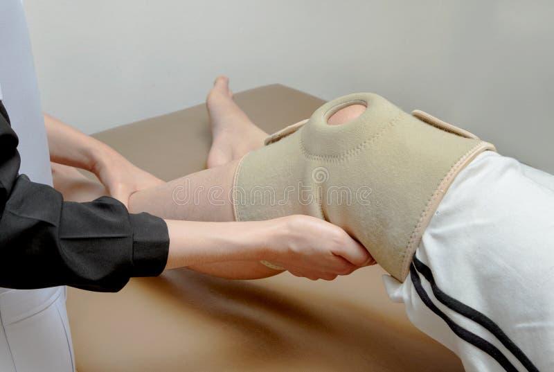 Fizyczny terapeuta stosuje kolanowego poparcie cierpliwy kolano, rehabil zdjęcie royalty free