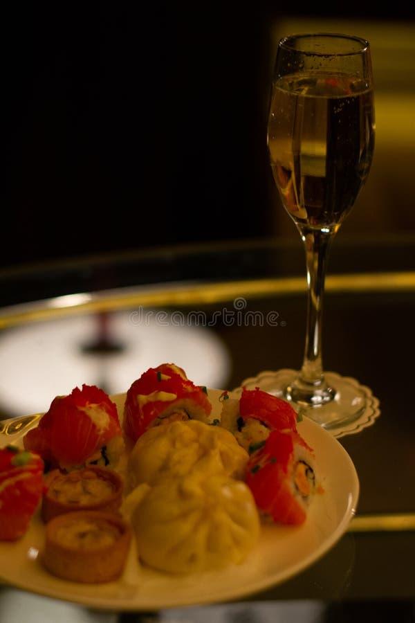 Fizzy champagne aperitif met pre-diner canapes zoals mini quiches, chinese konijnen en sushi stock afbeeldingen