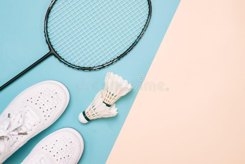 Fjäderboll- och badmintonracket med sportskor på pastellfärgad colo arkivbilder
