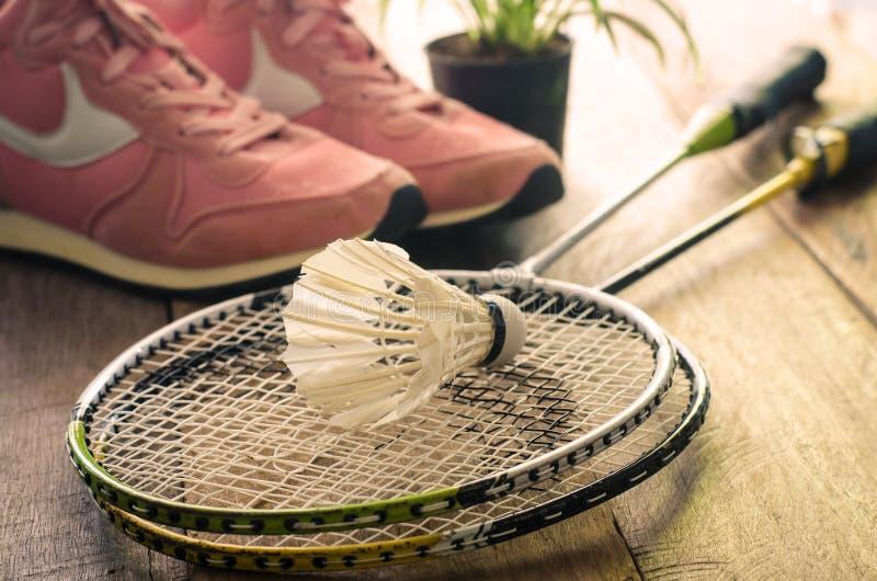 Fjäderboll- och badmintonracket med sportskor på trägolvet för övning arkivfoto