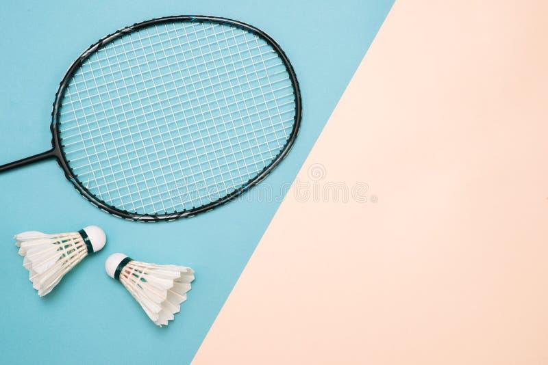 Fjäderboll och racket för att spela badminton på en färg för pá stel royaltyfri fotografi