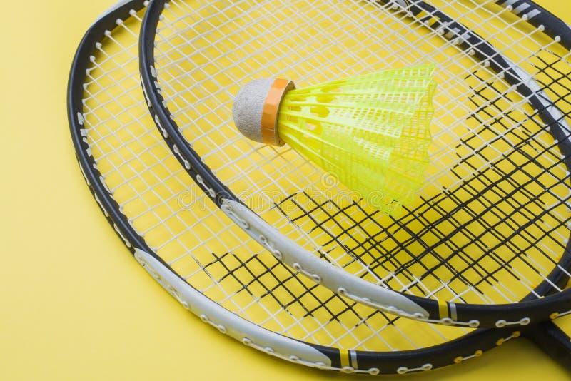 Fjäderboll och racket för att spela badminton på en gul bakgrund Begreppssommarferier arkivfoton