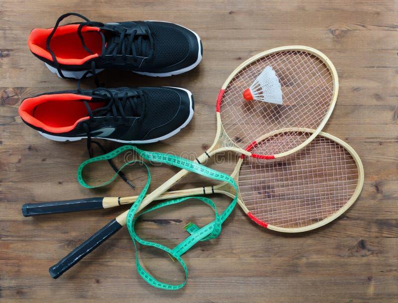 Fjäderbollar och badmintonracket med sportskor royaltyfria bilder
