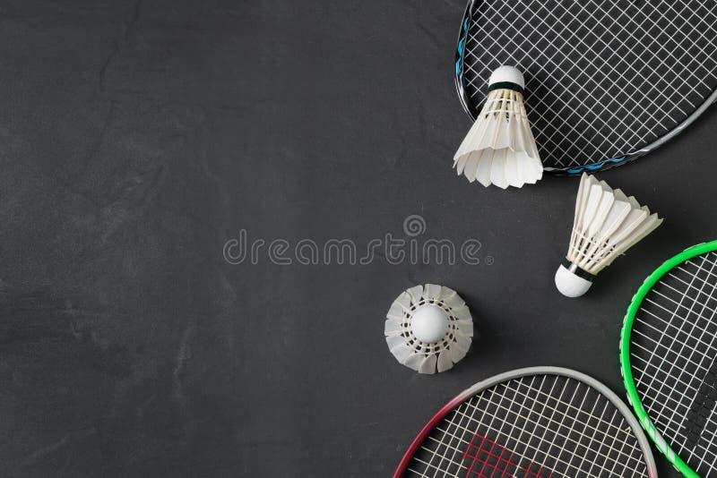 Fjäderbollar och badmintonracket på svart bakgrund arkivbild