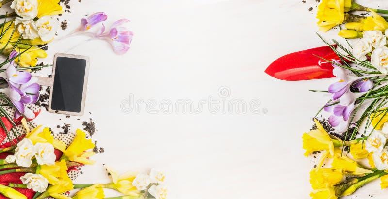 Fjädra arbeta i trädgården bakgrund med det trädgårds- tecknet, handskyffeln och blommor: påskliljor och krokusar på vit träbakgr royaltyfri foto
