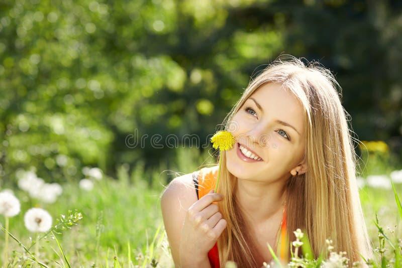 Fjädra flickan som ligger på fältet av maskrosor fotografering för bildbyråer